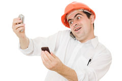 Busy businessman wearing a helmet with a phones Stock Photography
