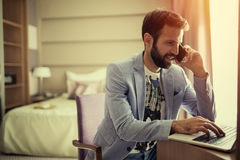 Busy businessman working from home. On laptop and phone Royalty Free Stock Photo