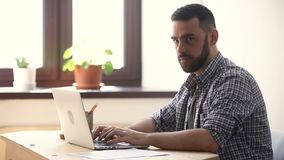 Busy serious businessman working on laptop, looking at camera smiling stock video
