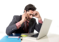 Busy businessman working in stress on computer laptop talking on mobile phone Stock Photos