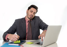 Busy businessman working in stress on computer laptop talking on mobile phone Stock Images