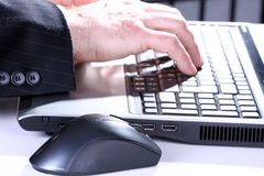 Busy businessmen. Close-up of hand typing on a lap top royalty free stock photos