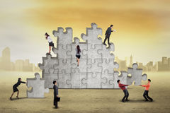 Busy businesspeople arrange puzzle royalty free stock photos