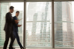 Busy businesspeople walking in office building, full-length wind. Busy businesspeople in office building, two businessmen walking along hallway, full-length Stock Photos