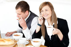 Busy businesspeople working during breakfast Royalty Free Stock Image