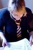 Busy Businesswoman. Woman in casual business dress, looking through paperwork Royalty Free Stock Photos