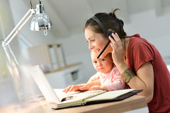 Busy businesswoman with baby working on laptop Royalty Free Stock Photo