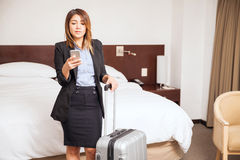 Busy businesswoman during a business trip. Beautiful sales executive checking his cell phone while arriving at her hotel room during a business trip Royalty Free Stock Photography