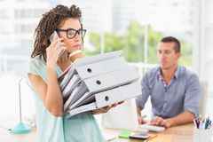 Busy businesswoman carrying a stack of folders Royalty Free Stock Image