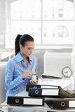 Busy businesswoman having coffee at desk Royalty Free Stock Images