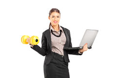 Busy businesswoman holding a laptop and lifting a dumbbell Stock Photo
