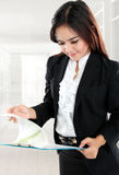 Busy businesswoman open paper and holding clipboard in her offic Stock Photography