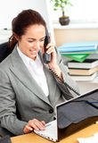Busy businesswoman phoning and using her laptop Stock Photo