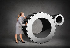 Busy businesswoman pushing cogwheel Stock Photos