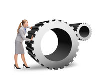 Busy businesswoman pushing cogwheel Royalty Free Stock Image