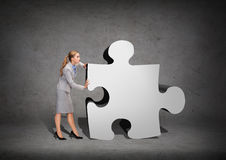 Busy businesswoman pushing puzzle piece Royalty Free Stock Image