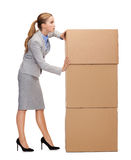 Busy businesswoman pushing tower of cardboards. Business, post and transportation concept - busy businesswoman pushing tower of cardboards Royalty Free Stock Image