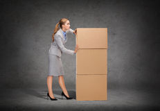 Busy businesswoman pushing tower of cardboards Royalty Free Stock Photo