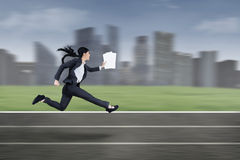 Busy businesswoman running fast stock images