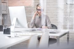 Busy Businesswoman Speaking by Phone Royalty Free Stock Image
