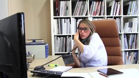 Busy businesswoman talking with cell and fixed line phone in office stock video