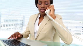 Busy businesswoman talking on phone and using laptop at desk stock footage