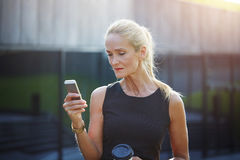 Busy businesswoman texting. Portrait of mature busy businesswoman standing outside texting Stock Photo