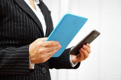 Busy businesswoman using digital tablet and mobile phone at he s Stock Images
