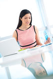 Busy businesswoman. Vertical image of a business lady analyzing documents while lunch royalty free stock image