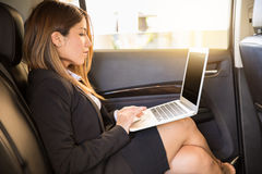 Busy businesswoman working in a car Royalty Free Stock Photo