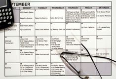 Busy Calendar, PDA & Glasses. This is an image of a busy calendar with glasses and a PDA royalty free stock photo
