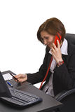 Busy call. Busy young businesswoman talking on the telephone while checking her mobile diary Royalty Free Stock Photos