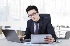 Busy caucasian worker with laptop and tablet Royalty Free Stock Image