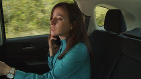 Chatting on phone businesswoman riding in car. Busy with cellphone confident female business executive riding on back seat of car, checking the time on stock video footage