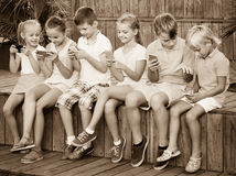 Busy children holding smartphones and sitting. Busy children holding smartphones in hands and sitting together outdoors Stock Image