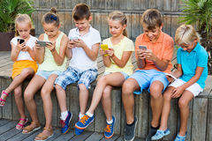 Busy children holding smartphones  and sitting Royalty Free Stock Image
