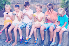 Busy children holding smartphones and sitting. Serious children holding smartphones in hands and sitting together outdoors Royalty Free Stock Photo