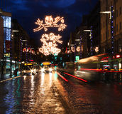 Busy Christmas street. City street with Christmas light decoration and busy traffic Royalty Free Stock Image