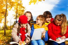 Busy clever kids in the park. Group of kids sitting together and discussing holding papers on the bench on autumn park Royalty Free Stock Photo
