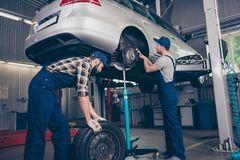 Busy colleagues professionals in special blue safety overalls un. Iform, head wear are torquing lugs nuts of wheel and rolling new rubber tyre, transportation is Stock Photo