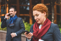 Busy colleagues using smartphones on street Stock Photography