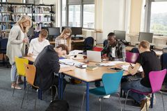 Busy College Library With Teacher Helping Students At Table stock image