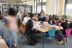 Busy College Library With Teacher Helping Students At Table royalty free stock images