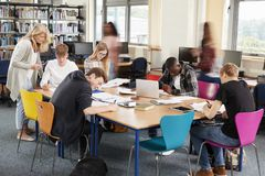 Busy College Library With Teacher Helping Students At Table stock photo