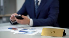 Busy company CEO taping on smartphone, working on presentation in office stock image