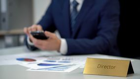 Busy company director using smartphone, making calculations for business report stock photo