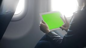 Woman working on modern tablet and talking in airplane stock video