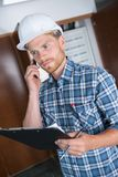 Busy construction engineer talking on phone and holding clipboard stock photos