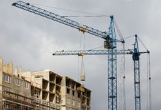 Busy Construction site. Apartment block under construction with two working cranes elevating cargo Royalty Free Stock Images
