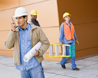 Busy construction workers carrying ladder. Blueprints and talking on cell phone Stock Photography